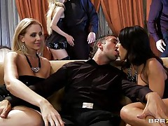 A blond and a darksome brown are rubbing a guy's crotch whilst sitting on a couch. They pull out his cock and start to suck it, every awaiting her turn. One more dick enters the scene and the darksome brown goes to blow it.