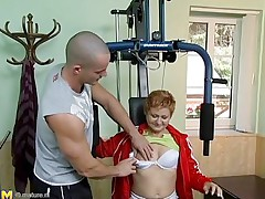 Watch this hot red headed cougar who takes advantage of this young gym instructor. That babe has great sex experience and begins seducing him, like that babe well knows. This old hottie has all that babe needs to make a man happy. That babe begins taking off her clothing to turn the young stud on. He likes playing with her tits.